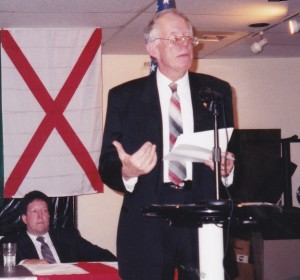Dr. William Pierce addressing an AF-BNP meeting in Arlington, Virginia in August 1999.   Don Wassall, editor of the Nationalist Times is seated to his left.