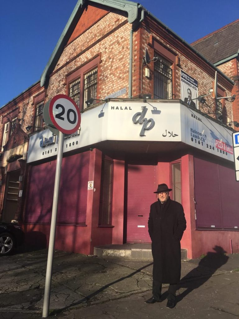 George Galloway visiting the Levenshulme area of the Gorton constituency on March 6th. Behind him is an old campaign poster for the 2015 (Asian) Conservative general election candidate in Gorton.